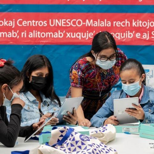 Descripción de la foto: Cuatro mujeres con mascarilla ven las tablets que le han sido otorgadas. (Foto: Unesco)